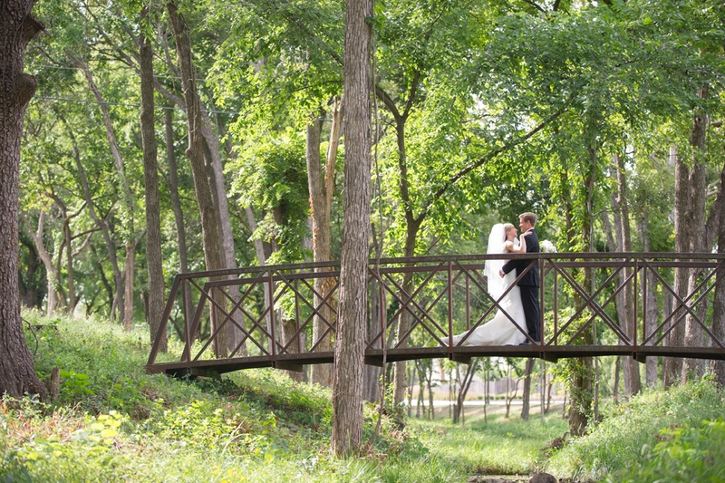 bride and groom on bridge in forest