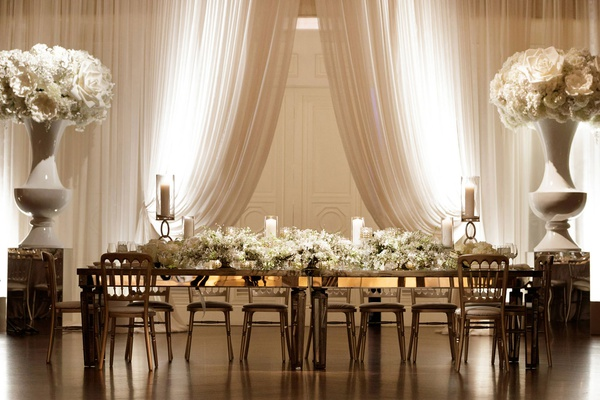 Wedding reception head table white drapery urn oversized flower decor long white flower runner