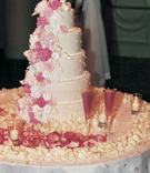 Pink florals cascade down wedding cake