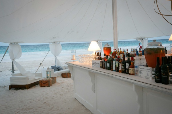 Ocean view tent wedding white bar with white lounge furniture on sand beach in the Bahamas
