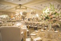Wedding reception with round table, gold sequined tablecloth, chairs, love seats, peach, pink, roses