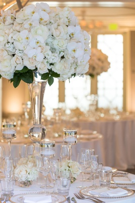 Close up of tall white wedding centerpiece rose, hydrangea, rochid flowers and green leaves