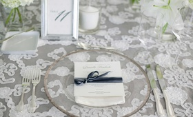 white lace table linen and clear glass plate with white and gray placecard reception
