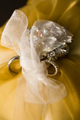 rings tied to yellow pillow with white ribbon