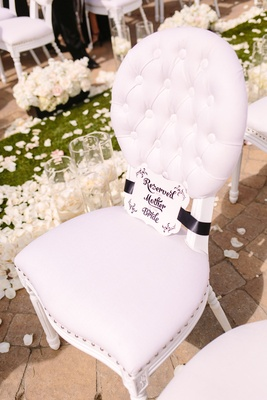 quilted cushioned white chair with reserved for mother of the bride sign
