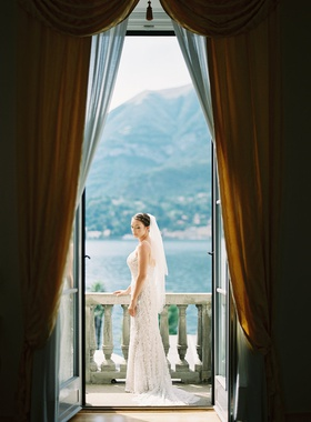bride on balcony in bridal suite lake como views veil hair up willowby by watters gown
