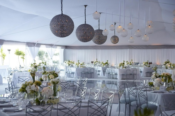 Tent wedding with globe lights and white flower decorations