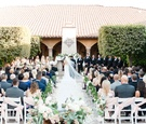 Bride and groom at end of aisle fireplace mantel altar with greenery along aisle wedding flowers