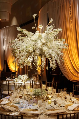 a full cascading floral arrangement centerpiece with different white flowers on a gold stand