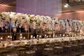 Wedding reception crystal ceiling installation with long head table flowers floating overhead candle