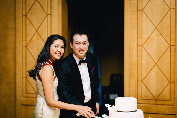 Bride in a white Qipao with gold embroidery and red trim cuts cake with groom in black tuxedo