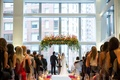Daytime wedding in new york city hotel lucite columns and flowers foliage floating above couple