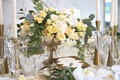 centerpiece in gold container, small yellow roses, white flowers, eucalyptus leaves, ivy