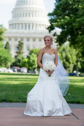 Blonde bride holding bouquet in front of U.S. Capitol
