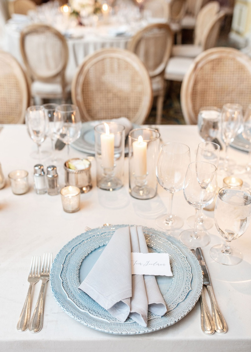 wedding reception place setting light blue charger plate grey napkin place card candles cane chair