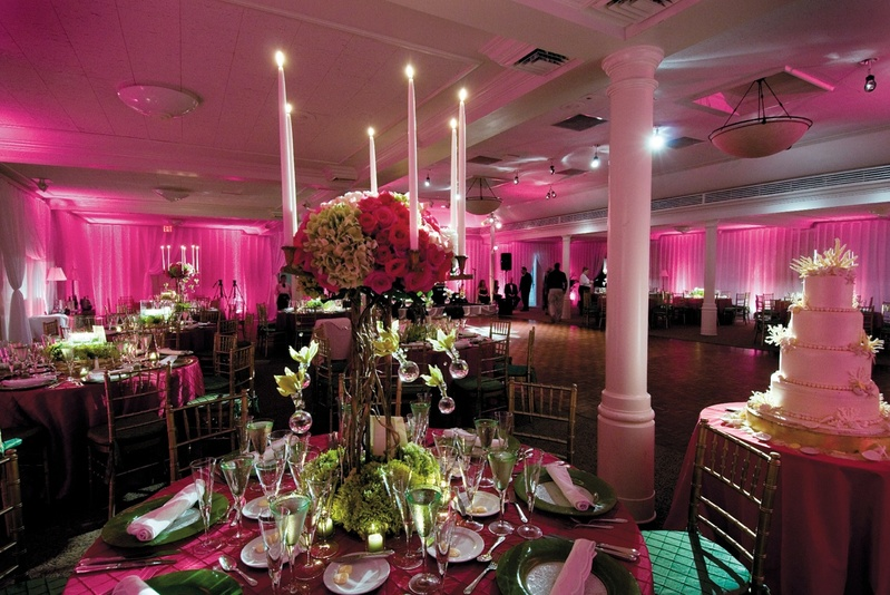 pink lighting and linens with green and pink flowers and white candles