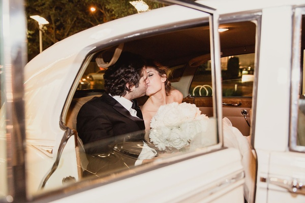 Groom kissing bride in getaway car after wedding grand exit bridal gown bouquet