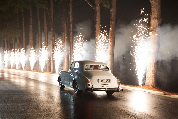 Bride and groom in white rolls-royce car classic white with firework fountains lining path to exit