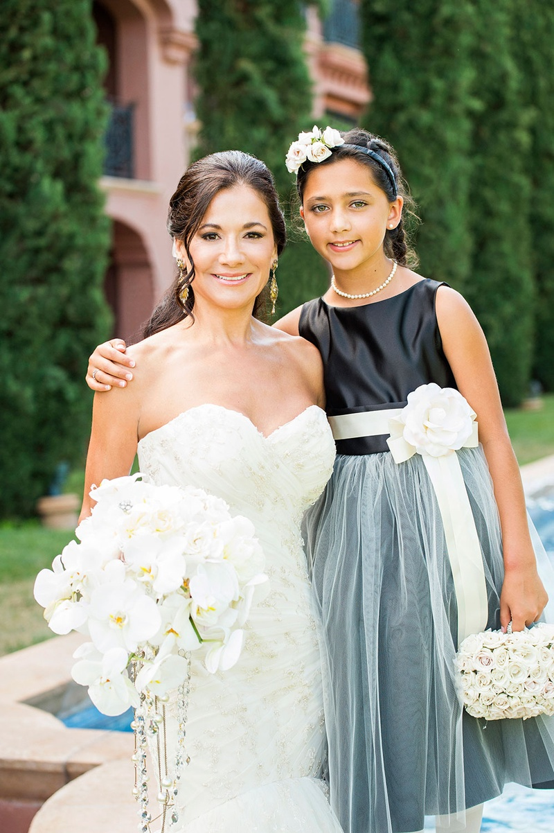 bride in strapless Romona Keveza wedding dress with flower girl in black and blue dress