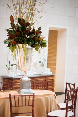 Silver urn wedding centerpiece with magnolia leaves and cattail
