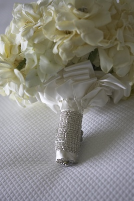 white flower bouquet wrapped with white satin ribbon