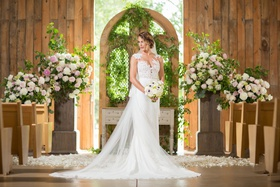 bride in pronovias gown with illusion neckline lace bodice, barn wedding ceremony