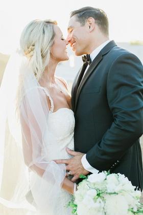 bride in galia lahav groom in men's wearhouse about to kiss long veil