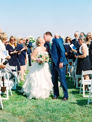 Wedding outdoors grass lawn white chairs for guests groom in blue suit bride in strapless dress kiss