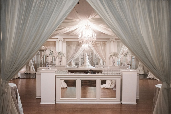 Mirror four sided bar with chandelier and drapes overhead white flowers lights white flowers