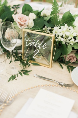 Wedding reception table number modern calligraphy on wood table gold geo frame clear translucent