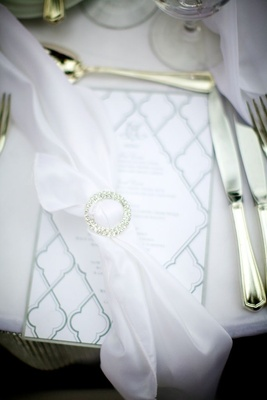 White napkin tied with crystal ring on menu card