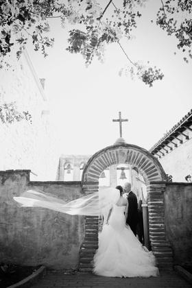 black and white photo of bride in romona keveza kisses groom at mission San Juan Capistrano