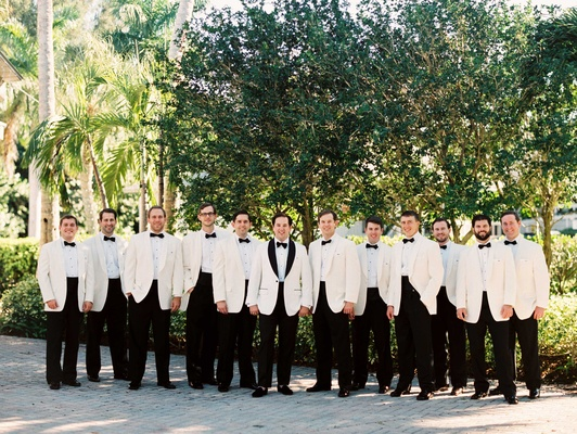 Groom in white tuxedo jacket black lapels and groomsmen in ivory jackets black bow ties