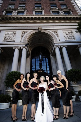 Bride in a strapless Alvina Valenta gown and black sash with bridesmaids in tea-length black dresses