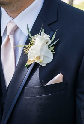 pink and blue groom outfit orchid boutonniere white flower leaves green pocket square