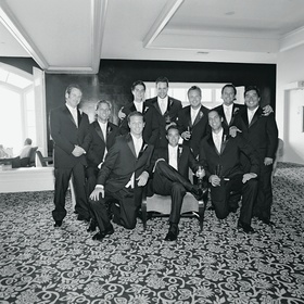 Black and white photo of groomsmen and groom in hotel room