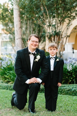 Groom On One Knee With Ring Bearer In Cummerbund Black White Bow Tie And Tuxedo Wedding