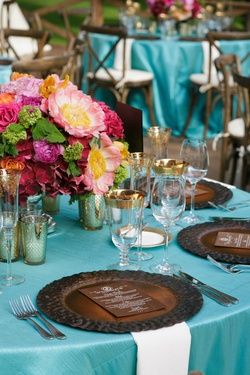 Wedding reception table with dark brown plate and menu with wood background