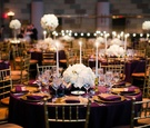 Round wedding reception table with purple linen, gold plates, tall candles, and white flowers