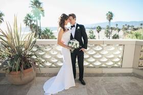 bride in j. mendel wedding dress, groom in suitsupply suit, newlyweds at balcony overlooking beach
