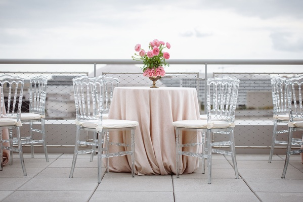 Wedding cocktail hour tables with light pink linens and flowers clear chairs white cushions