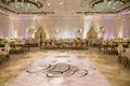White wedding reception ballroom rose gold chairs monogram dance floor flowers hanging from ceiling