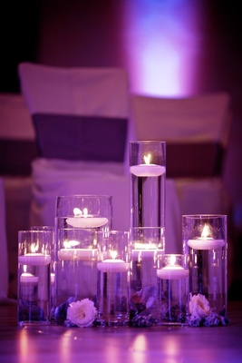 Purple lighting on candle-filled cylindrical vases