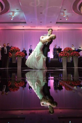 Groom dips bride on dance floor with reflection