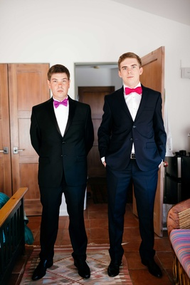 grooms standing wearing black suits and purple and red bow ties double wedding