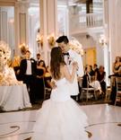 bride in wedding dress trumpet gown white tuxedo jacket groom gold monogram dance floor chandelier