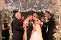 Jewish wedding with bride and groom under chuppah tallit fathers winter lights flowers white silver