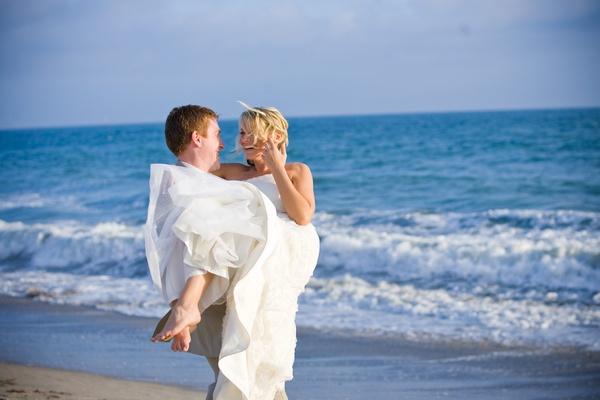 Wedding photo of groom picking up bride on beach