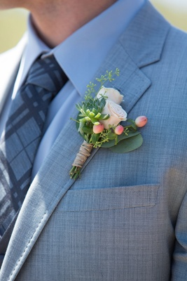 Groom in grey suit with pattern tie and rustic boutonniere succulent small rose buds berries green