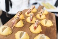 Hors d'oeuvres at cocktail hour on wood cutting board yellow lemon halves wedged out for tacos